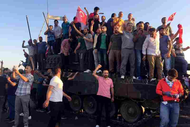 People climb on tanks after soldiers occupying Bosphorus Bridge surrendered in Istanbul, Turkey on Saturday.