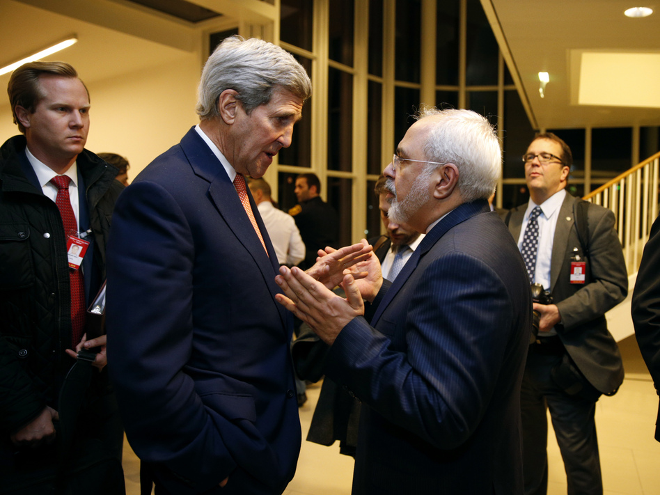 Secretary of State John Kerry talks with Iranian Foreign Minister Mohammad Javad Zarif in Vienna on Jan. 16, after the International Atomic Energy Agency verified that Iran met all conditions under the nuclear deal. The accord is now 1-year-old. Iran is seen as abiding by requirements of the deal, but its relations with the U.S. and other rivals have not improved on other fronts. (Kevin Lamarque/AP)