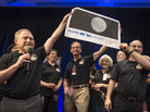 Members of the New Horizons team celebrated last year with a blown-up image of the postage stamp when the probe made its closest approach to Pluto.