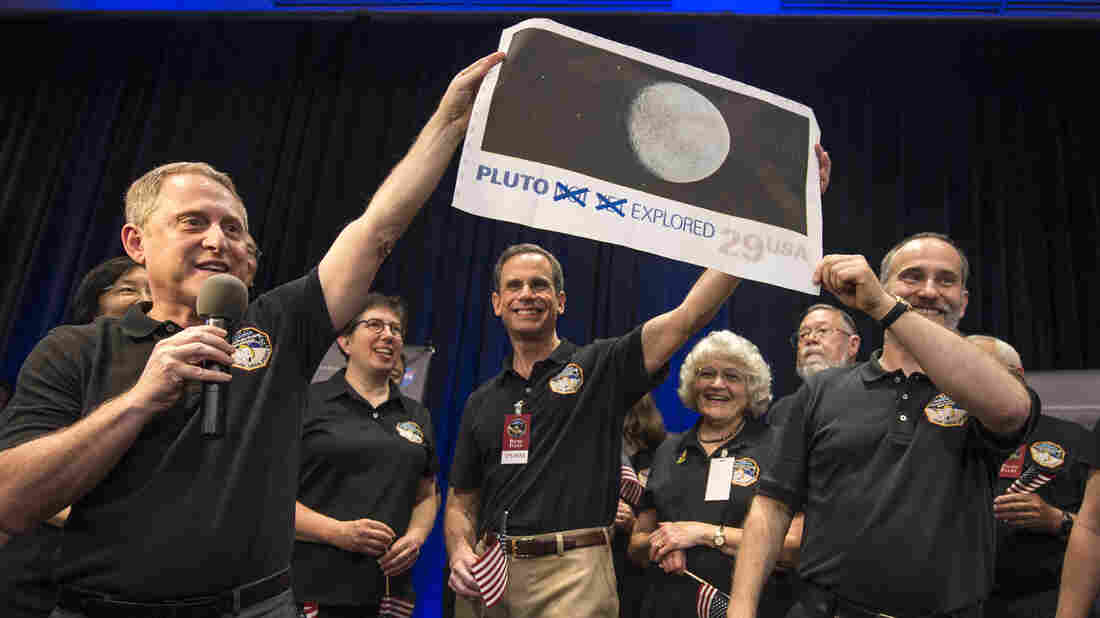 Members of the New Horizons team celebrated last year with a blown up image of the postage stamp when the probe made its closest approach to Pluto.