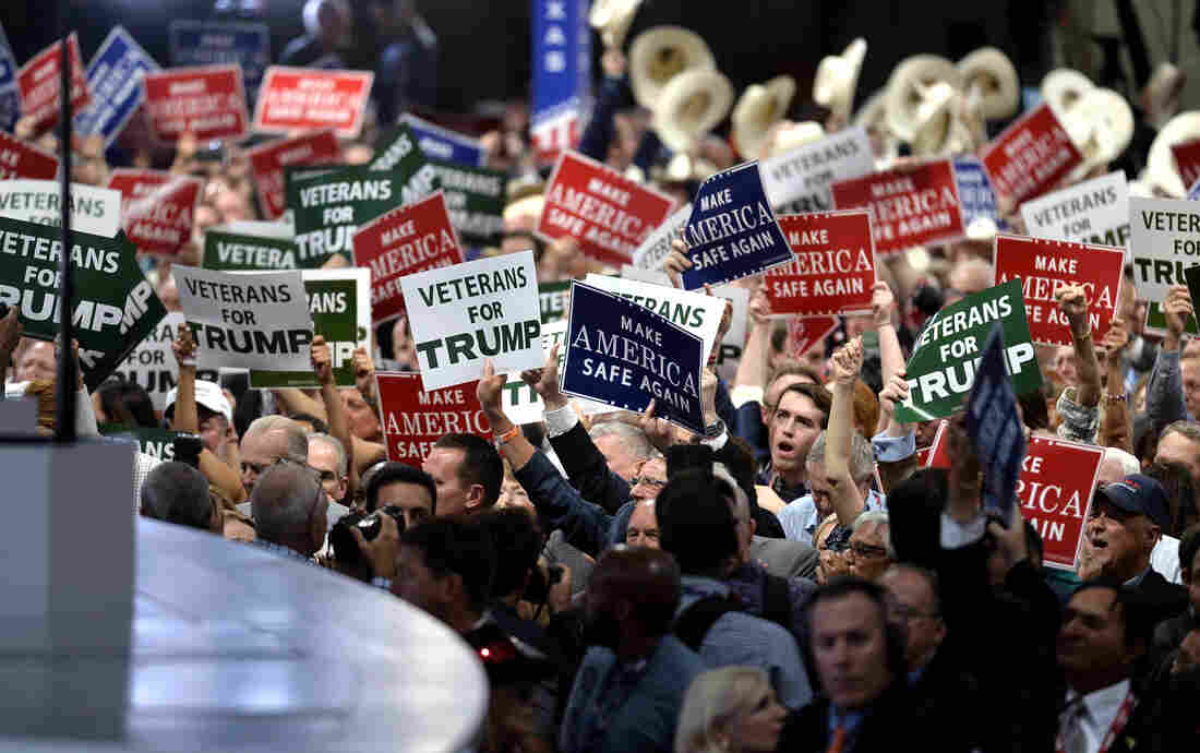 Delegates hold signs on the first day of the Republican National Convention on Monday evening at the Quicken Loans Arena in Cleveland, Ohio.
