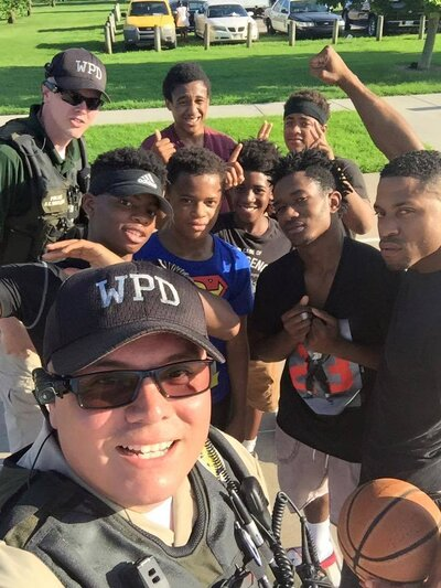 Officers pose with young men on a basketball court during a community cookout in Wichita, Kan.
