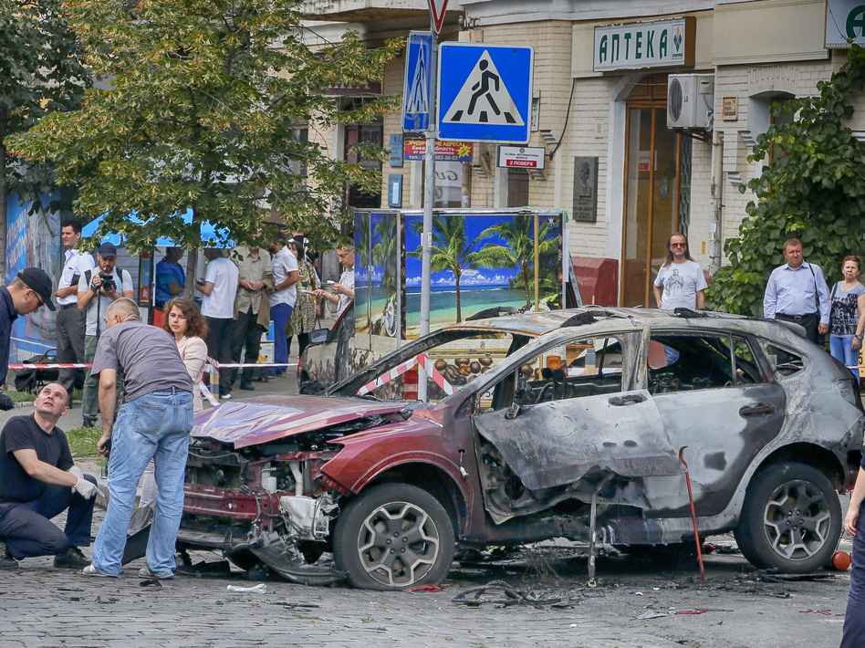 Forensic experts examine the wreckage of a burned car in Kiev, Ukraine. Pavel Sheremet, a prominent investigative journalist, was killed when the car exploded on Wednesday.