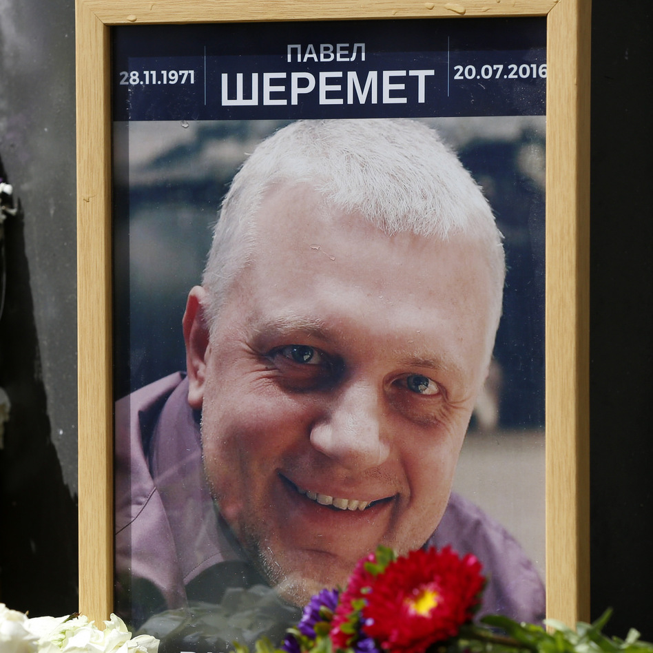 A portrait of journalist Pavel Sheremet is surrounded with flowers and candles near where the car he was driving exploded, killing him on Wednesday. (AP)