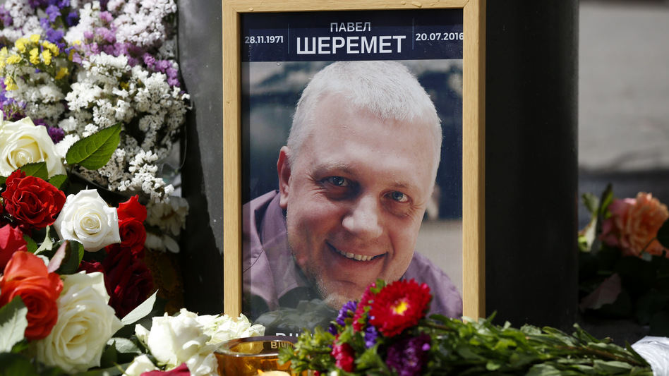 A portrait of journalist Pavel Sheremet is surrounded with flowers and candles near where he was killed. (AP)