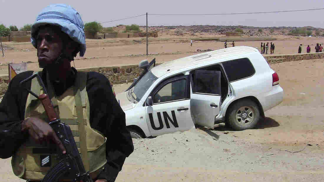 A soldier of the United Nations mission to Mali stands guard near a UN vehicle after it drove over an explosive device near Kidal, northern Mali, on July 14.