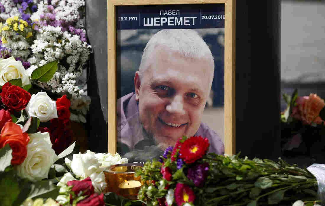 A portrait of journalist Pavel Sheremet is surrounded with flowers and candles at the place where he was killed by a car bomb Wednesday in Kiev, Ukraine.