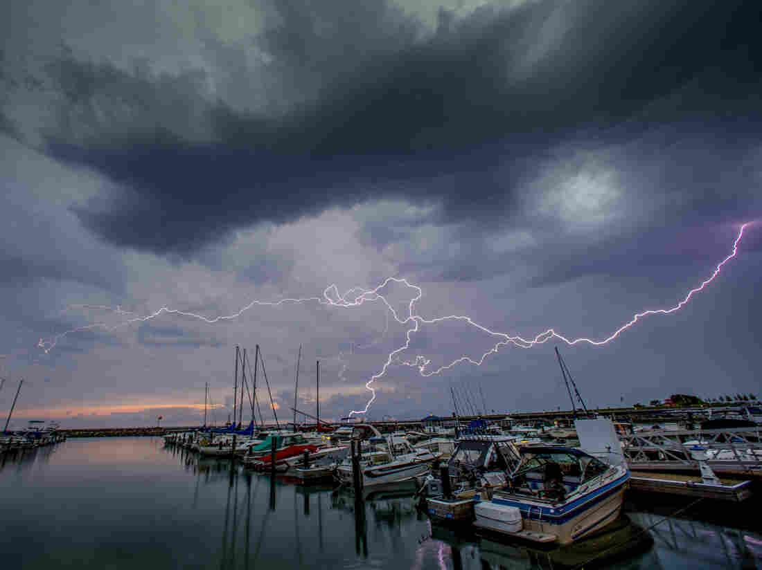 "Lightning streaks across the sky over Port Washington, Wis., on Thursday. A phenomenon called a ""heat dome"" is causing temperatures well above 100 degrees, according to the National Weather Service."