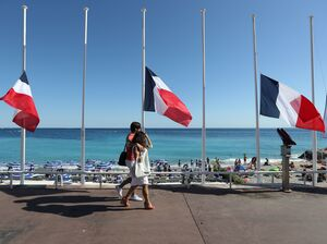 "French flags are seen lowered at half-staff in Nice on July 16. The truck attack on July 14 killed 84 people. ""I felt coming to celebrate on holiday and people are in mourning didn't seem right,"" one vacationer says. ""But I'm glad I came."""