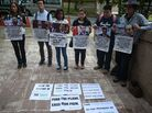 Relatives of passengers on Malaysia Airlines Flight 370 hold placards following a joint news conference on the search for the missing airliner Friday. The search will be suspended if nothing turns up in the current area, officials say.