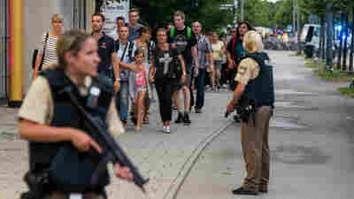 Police officers escort people from inside the shopping center as they respond to a shooting in Munich. Police believed shooters were still at large and urged residents to stay indoors.