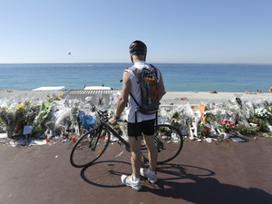 A cyclist looks at the flowers and messages placed along the beach for victims of the recent terrorist attack in Nice, France, on Wednesday. The recent spate of attacks around the world has raised questions about the limits of counterterrorism.