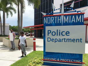 Gabriel Pendas (left) protests outside the North Miami Police Department on Thursday. The department held a news conference about the police shooting of a black behavioral therapist helping a man with autism.