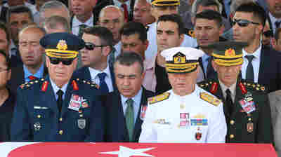 Turkish Land Forces commander Salih Zeki Colak (right), naval commander  Admiral Bulent Bostanoglu (second right) and air force commander Abidin Unal (left) attend a funeral in Ankara on July 18 for police officers killed during the failed July 15 coup attempt.