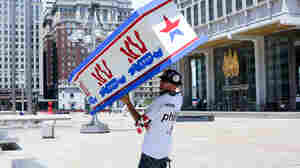 """Bernie Sanders supporter and organizer Billy Taylor held a coffin painted with donkeys during a march Sunday in Philadelphia. He told NPR he applied for protest permits to """"stop any Hillary supporters from obtaining permits."""""""
