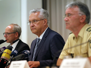Bavarian Interior Minister Joachim Herrmann (center), briefs the media in Ansbach, Germany, Monday July 25, 2016. Bavaria's top security official says a man who blew himself up after being turned away from an open-air music festival in Ansbach was a 27-year-old Syrian who had been denied asylum.