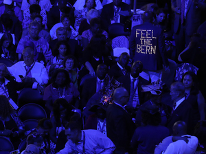 The lighted back of a Bernie Sanders supporter's jacket stands out among the delegates during the first day of the Democratic National Convention in Philadelphia on Monday.
