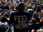 The lighted back of Bernie Sanders supporter Sanjay Patel's jacket stands out among the delegates during the first day of the Democratic National Convention in Philadelphia on Monday.