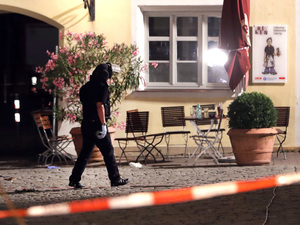 A special police officer examines the scene after an explosion in a public place in Ansbach, Germany, Monday. Bavaria's top security official says a man who blew himself up near an open-air music festival in the southern German city was a 27-year-old Syrian.
