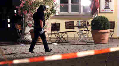 A special police officer examines the scene after an explosion struck a public place in Ansbach, Germany, Monday. Bavaria's top security official says a man who blew himself near an open-air music festival in the southern German city was a 27-year-old Syrian.