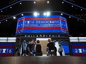 Workers prepare the podium on July 24 ahead of the Democratic National Convention at the Wells Fargo Center in Philadelphia, Penn.