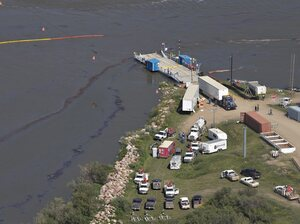 Crews work to clean up an oil spill on the North Saskatchewan River on Friday. Husky Energy has said between 200,000 and 250,000 liters of crude oil and other material leaked into the river on Thursday from its pipeline.