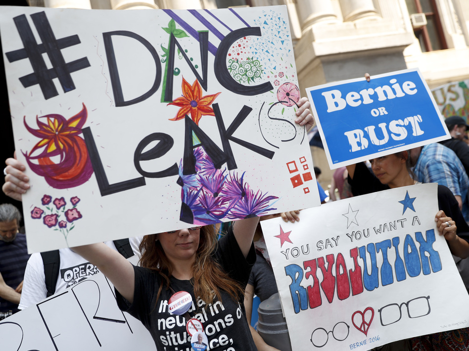 Demonstrators held signs outside the Democratic National Convention on Monday in Philadelphia. On Sunday, Debbie Wasserman Schultz, announced she would step down as DNC chairwoman at the end of the party's convention, after thousands of internal DNC emails were posted by the website Wikileaks. (John Minchillo/AP)