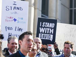 David Daleiden (left foreground) speaks to the media after appearing in court at the Harris County Courthouse on February 4 in Houston, Texas. All charges against Daleiden and his fellow anti-abortion activist Sandra Merritt have been dropped.