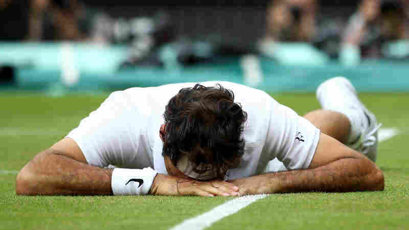Roger Federer of Switzerland reacts after slipping during a men's singles semifinal match during Wimbledon in London.