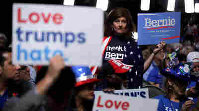 Delegates hold signs during the first day of the Democratic National Convention at the Wells Fargo Center on Monday in Philadelphia.