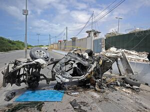 Somali soldiers stand guard next to the wreckage of a car bomb outside the U.N.'s office in Mogadishu on Tuesday. At least 13 people were killed in twin bombings near U.N. and African Union buildings adjoining Mogadishu's airport, police said, in what the jihadist al-Shabab group claimed as a suicide attack.