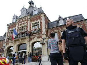 A French police officer stands guard by Saint-Etienne-du-Rouvray's city hall following a hostage-taking at a church in the small town on Tuesday. Two men with knives attacked the church, killing a priest, police say. Police said they killed two hostage-takers in the attack in the Normandy town, 77 miles north of Paris.