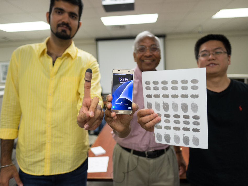 Michigan State University researchers Sunpreet Arora (left), Anil Jain (center) and Kai Cao (right) tried 3-D printed fingertips and 2-D fingerprint replicas on conductive paper to unlock a murder victim's phone, similar to one in the photo. (Derrick Turner/Michigan State University)