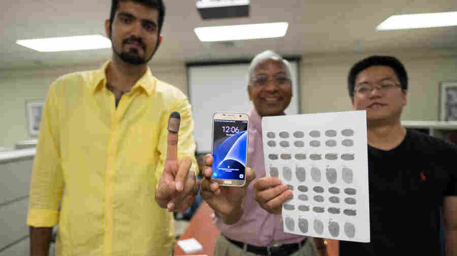 Michigan State University researchers Sunpreet Arora (left), Anil Jain (center) and Kai Cao (right) tried 3-D printed fingertips and 2-D fingerprint replicas on conductive paper to unlock a murder victim's phone, similar to one in the photo.