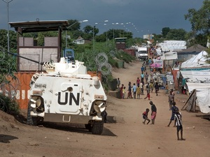 Some of the more than 30,000 Nuer civilians sheltering in a United Nations base in South Sudan's capital Juba for fear of targeted killings by government forces walk by an armored vehicle and a watchtower manned by Chinese peacekeepers.
