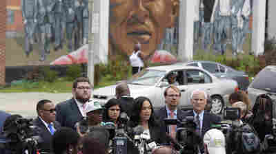 Baltimore State's Attorney Marilyn Mosby, center, speaks during a news conference Wednesday after her office dropped remaining charges against the three Baltimore police officers who were still awaiting trial in Freddie Gray' death. Third from left, in a cap, is Freddie Gray's father, Richard Shipley.