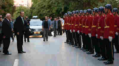 Turkey's President Recep Tayyip Erdogan (in suit and green tie), inspects a police honour guard as he arrives at the parliament in Ankara on Friday. A July 15 coup attempt was quickly crushed in Turkey, a country that has had multiple military takeovers in the past.
