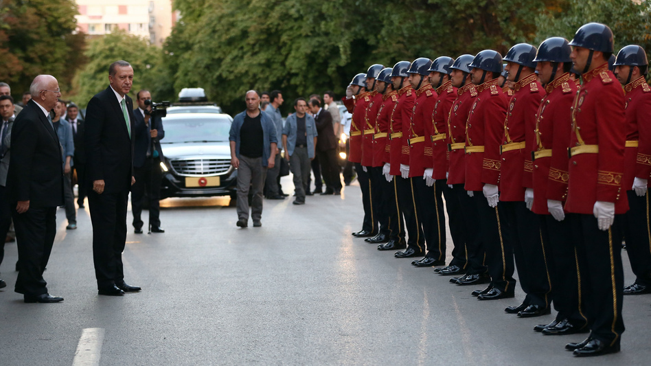 Turkey's President Recep Tayyip Erdogan (in suit and green tie) inspects a police honor guard as he arrives at the parliament in Ankara on Friday. A July 15 coup attempt was quickly crushed in Turkey, a country that has had multiple military takeovers in the past. (AP)