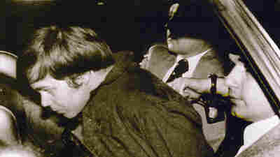 John Hinckley Jr. is escorted by police in Washington, D.C., following his arrest after shooting and seriously wounding president Ronald Reagan in 1981.