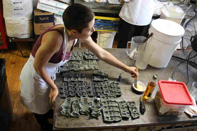 Candy maker Mariel Celentano oils the molds to prevent the candy mixture from sticking.