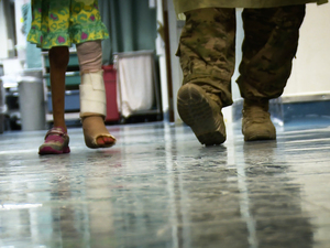 Ameera, 6, walks with assistance at the Craig Joint Theater Hospital at Bagram Airfield, Afghanistan. She is recovering from a gunshot wound when she was caught in a firefight between American and Afghan soldiers and Taliban insurgents.