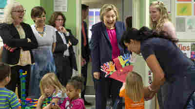 A 3-year-old presents her artwork to Hillary Clinton at Lee Highway KinderCare in Fairfax, Va.