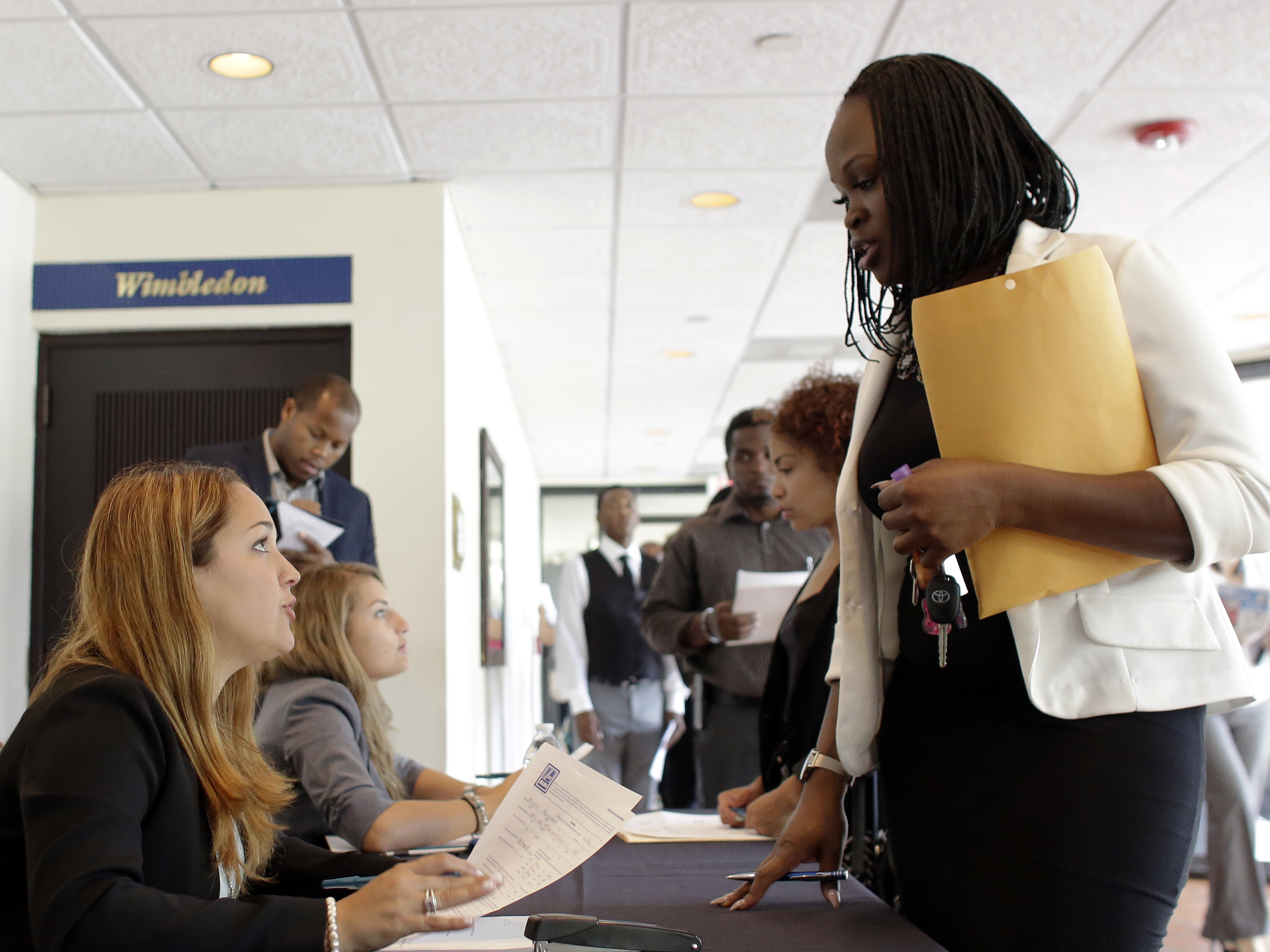 Claudia Caballero, a district manager for Aldi, talks with applicant Manoushka Metellus (right) at a job fair in Florida earlier this month. With a low unemployment rate, consumers are still spending but business inventories fell during the second quarter.