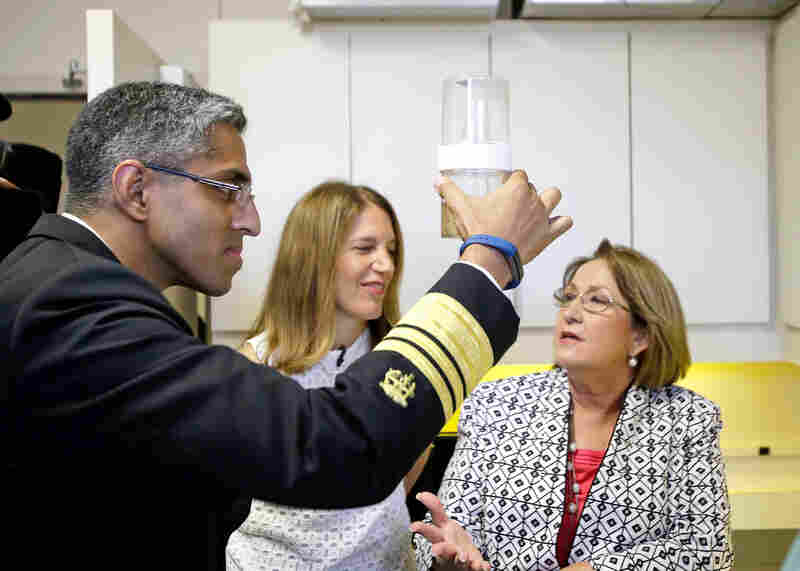 U.S. Surgeon General Vivek Murthy, left, looks at a container of mosquitos that could potentially carry the Zika virus with U.S. Department of Health and Human Services Secretary Sylvia Burwell, center, and Orange County Mayor Teresa Jaccobs while on a preparedness visit to Orange County Mosquito Control, Monday, July 25, 2016, in Orlando, Fla.
