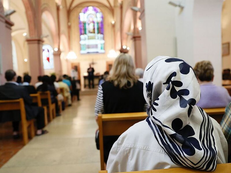 A Muslim faithful woman sits as she attends a Mass in tribute to priest Jacques Hamel at the Saint-Leu Saint-Gilles Bagnolet's Church, near Paris on Sunday.