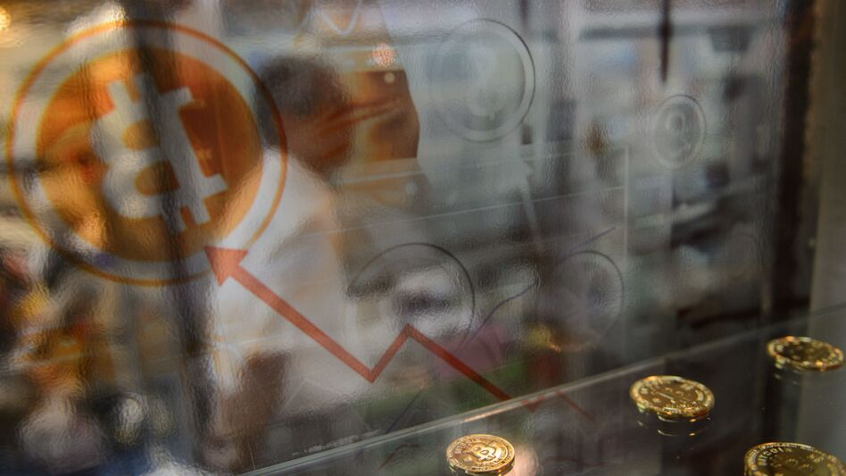 A man walks past a display cabinet containing models of bitcoins in Hong Kong on Wednesday. (Anthony Wallace/AFP/Getty Images)