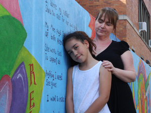 Savannah Phelan, 8, and her mom, Kellie, in front of a 77-foot mural they helped paint, which reflects the experiences of children and teenagers affected by incarceration.