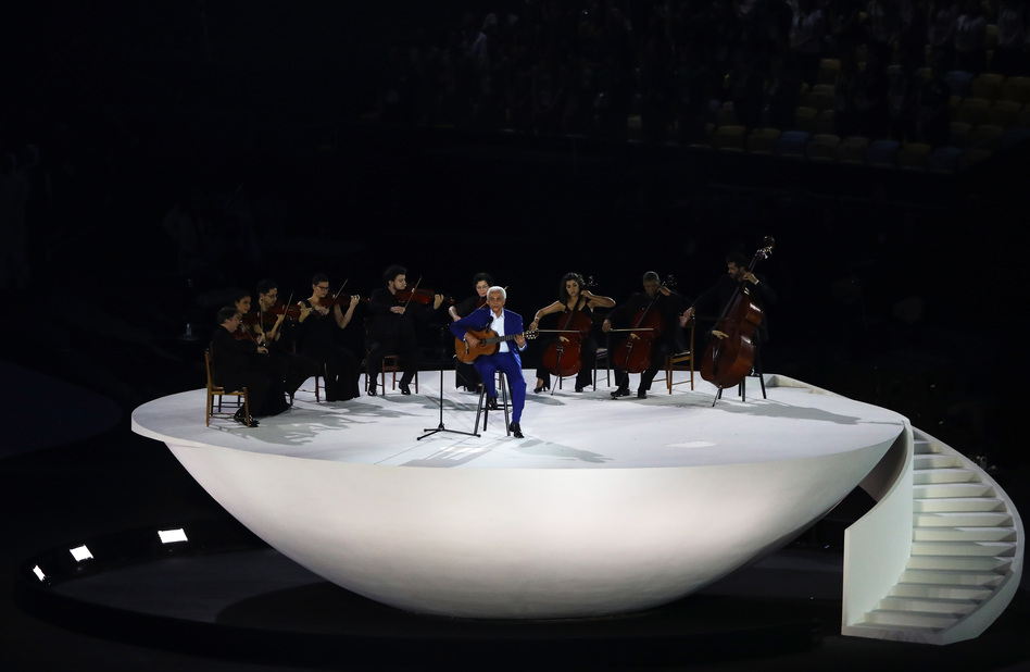 Musician Paulinho da Viola plays (and sings) the national anthem on acoustic guitar, accompanied by the audience and a small string orchestra. (Getty Images)