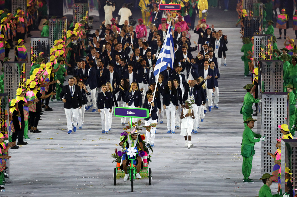 Athletes come out led by a tricked-out florescent three-wheeled bicycle. As is customary at the Olympics, the first delegation out of the gate is that of Greece. (Getty Images)