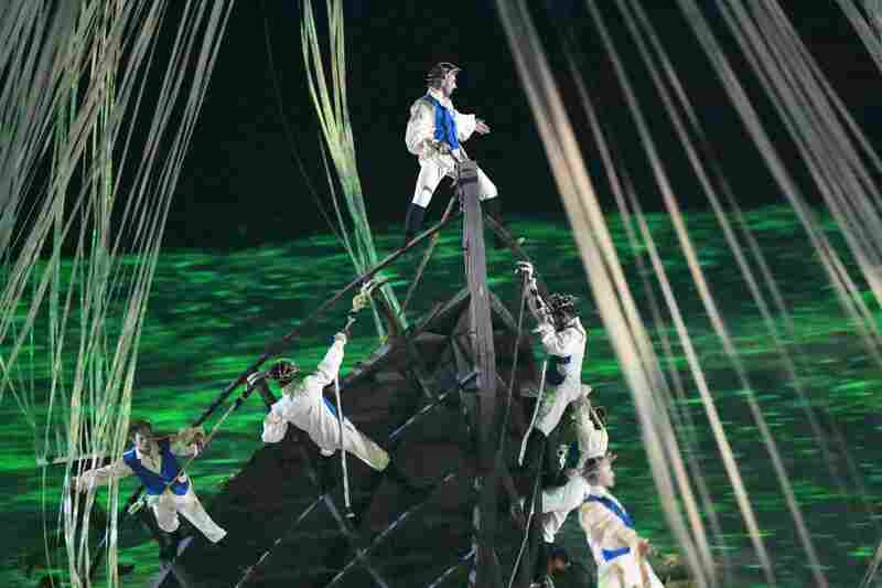 Acrobats simulate the arrival of Europeans in ships, three mechanical Caravels, where they meet indigenous people.